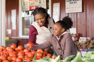 A grandmother and granddaughter choosing tomatoes