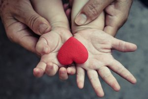 old hands holding young hand of a baby with red heart - family love and warmth concept