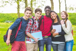 Group of multiethnic teenage students embraced together at park. Two boys and one girl are caucasian, one boy and one girl are black. Friendship, immigration, integration and multicultural concepts.
