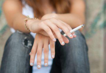 Teenage hands holding cigarette outdoor.