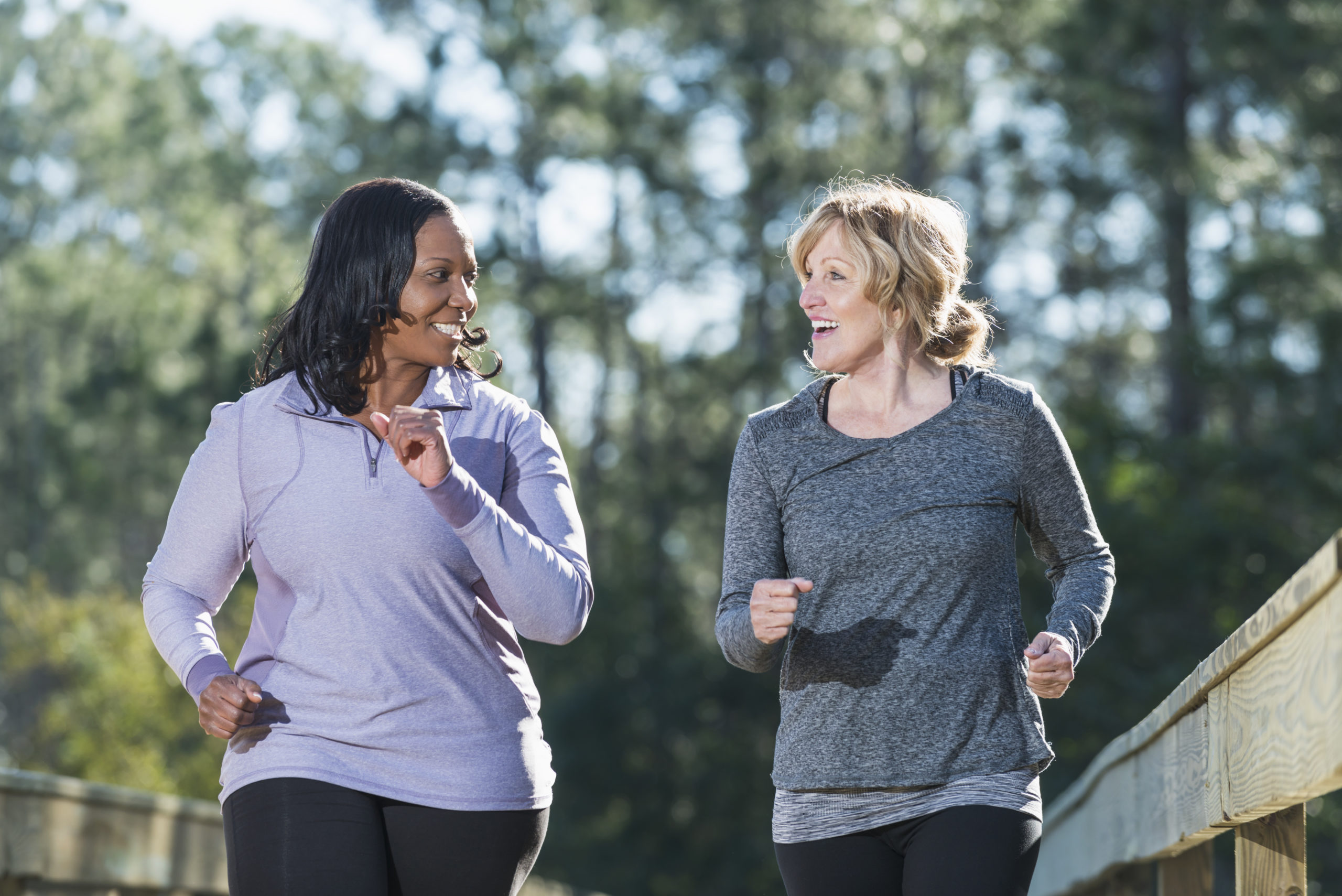 Mature women (40s, 60s) jogging in park.