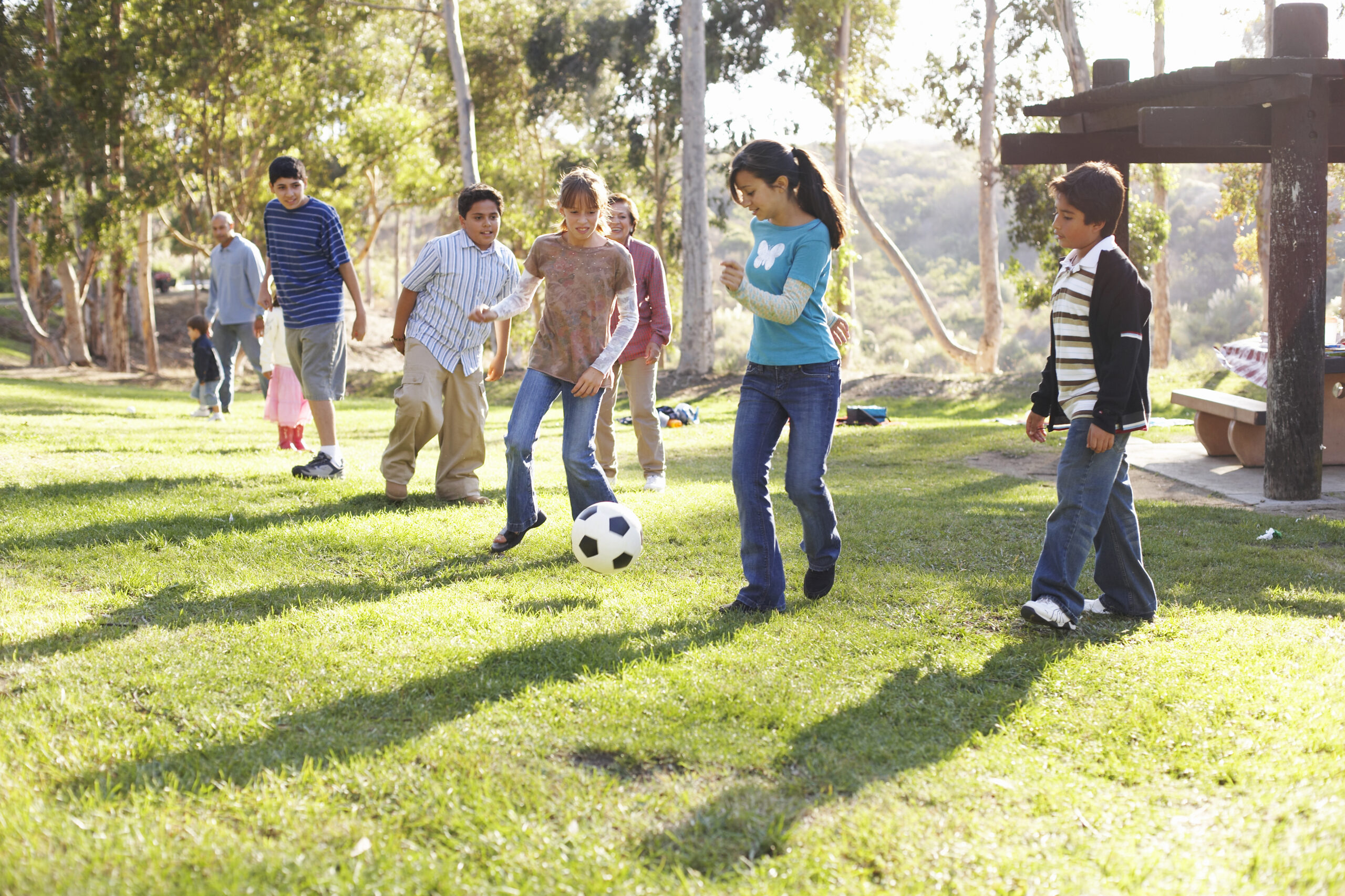Children (9-14) playing soccer in park